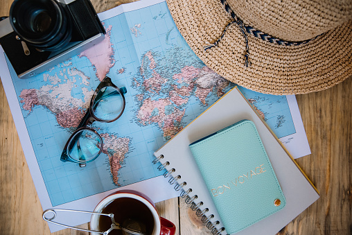 Travel preparations essentials. World map, cup of tea, vintage film camera, hat, passport, notebook and stylish glasses on the old rustic wooden table background, flat lay