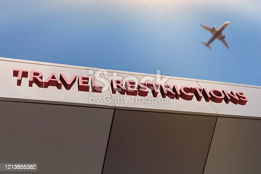 Travel restrictions concept. Flights cancelled and unavailable amid COVID-19 chinese Wuhan pandemic virus outbreak. Airport entrance with TRAVEL RESTRICTIONS text. Blurred airplane in sky.