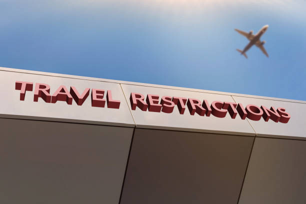 Travel restrictions concept. Flights cancelled and unavailable Travel restrictions concept. Flights cancelled and unavailable amid COVID-19 chinese Wuhan pandemic virus outbreak. Airport entrance with TRAVEL RESTRICTIONS text. Blurred airplane in sky. aground stock pictures, royalty-free photos & images