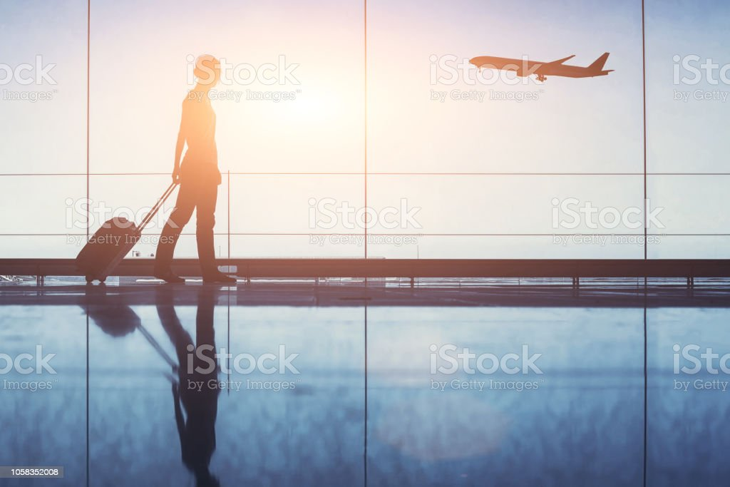Travel. Silhouette of woman passenger with baggage in airport. stock photo