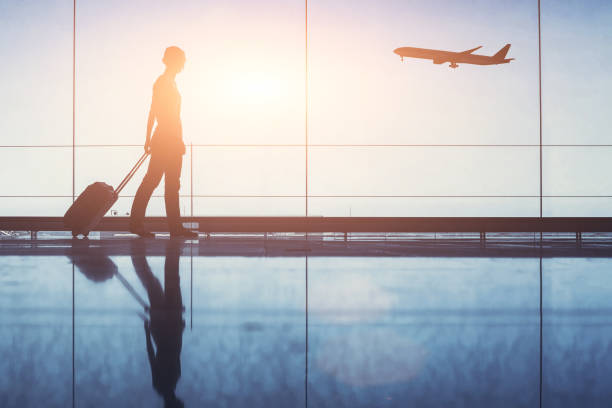 Travel. Silhouette of woman passenger with baggage in airport. people traveling, silhouette of woman passenger with baggage in airport air transport building stock pictures, royalty-free photos & images
