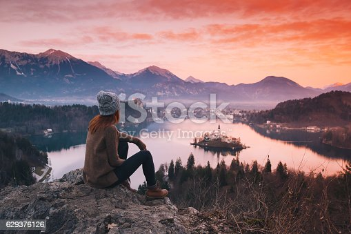 Travel Slovenia, Europe. Woman looking on Bled Lake with Island, Castle and Alps Mountain on background. Top view. Bled Lake one of most amazing tourist attractions. Sunset winter nature landscape.