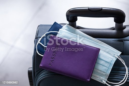 Travel suitcase, passport and medical mask. The ban on travel during the epidemic of coronavirus and global quarantine against covid-19 concept.