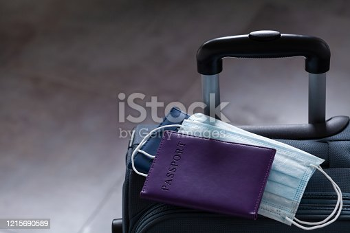 istock Travel suitcase, passport and medical mask. The ban on travel during the epidemic of coronavirus or covid-19 and the introduction of quarantine concept. 1215690589