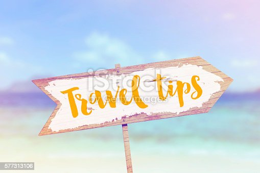 A wooden sign against summer beach background scene. The sign is arrow shaped pointing to the right. The sign has been painted white with the words travel tips written on.