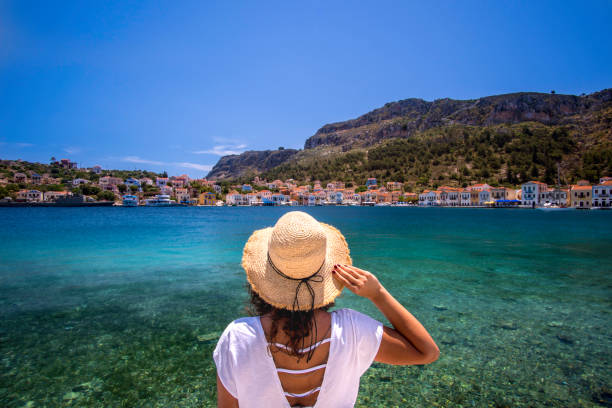 Travel to Greek Island Young woman at shore of Megisti (Kastellorizo) Island, Greece. mediterranean sea stock pictures, royalty-free photos & images