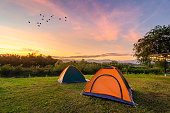 Travel to spread the tent in a wide open space in the evening. The golden sky mountain views on the Nakhasat Sabai In Chiang Mai Thailand