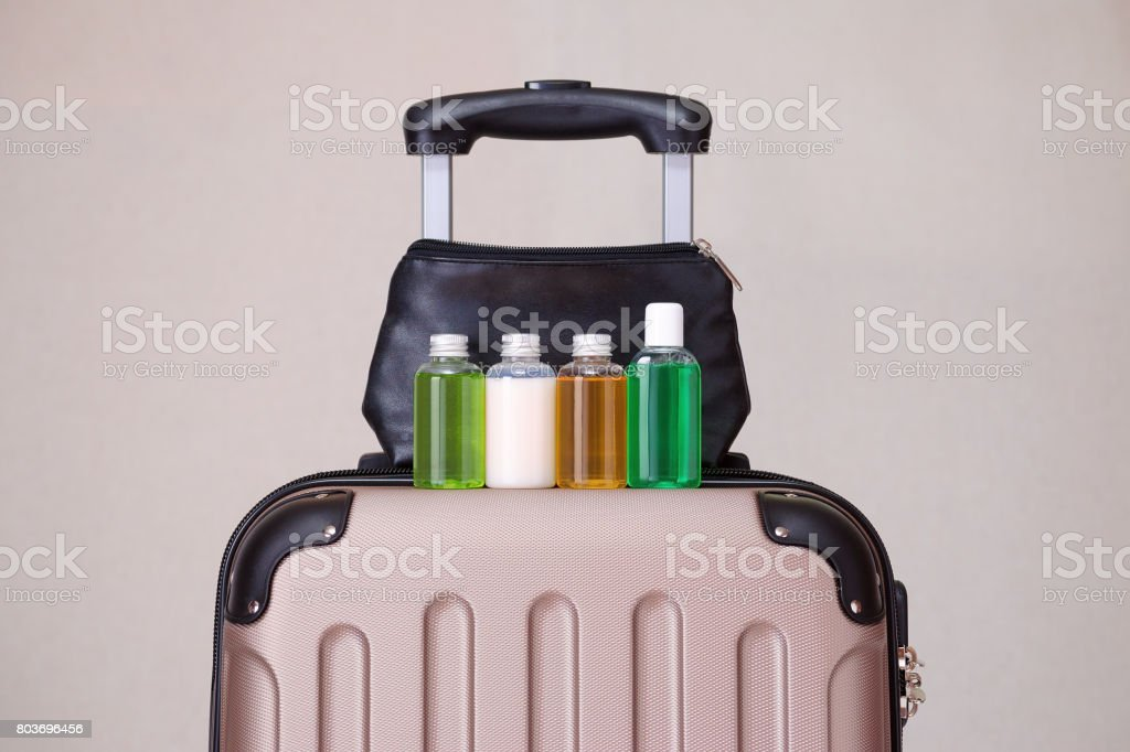 travel toiletries, small plastic bottles of hygiene products on the suitcase stock photo