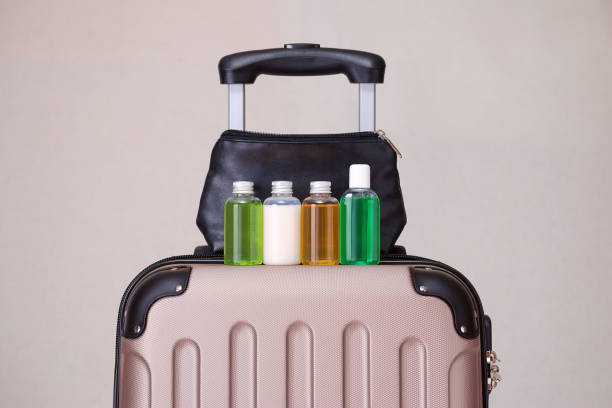 travel toiletries, small plastic bottles of hygiene products on the suitcase - przybory toaletowe zdjęcia i obrazy z banku zdjęć
