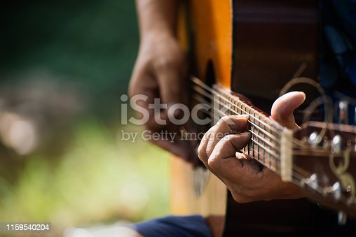 travel, tourism, hike, leisure concept -  Hipster guy classic guitar practice by hand, Happy man playing aoustic guitar at camping,close up,copy space for text.