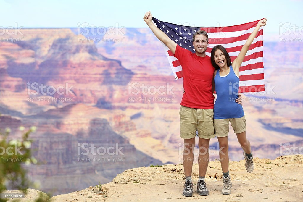 USA travel tourist couple holding american flag stock photo