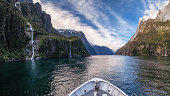 In Milford Sound cruise, one experience the spray of a waterfall close to sheer rock faces. A popular tourist destination and natural landscape in New Zealand. This view is breathtaking and iconic.