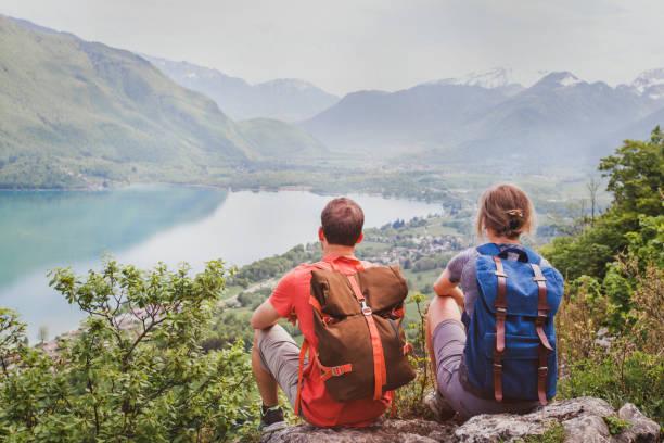 travel, two hikers enjoying beautiful panoramic mountain view, summer hiking - занятия на открытом воздухе стоковые фото и изображения
