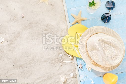 istock Travel vacation concept. Traveler accessories on sand. Straw hat, sunglasses, flip flops, cocktail, sunblock with copy space. Summer background 930712328