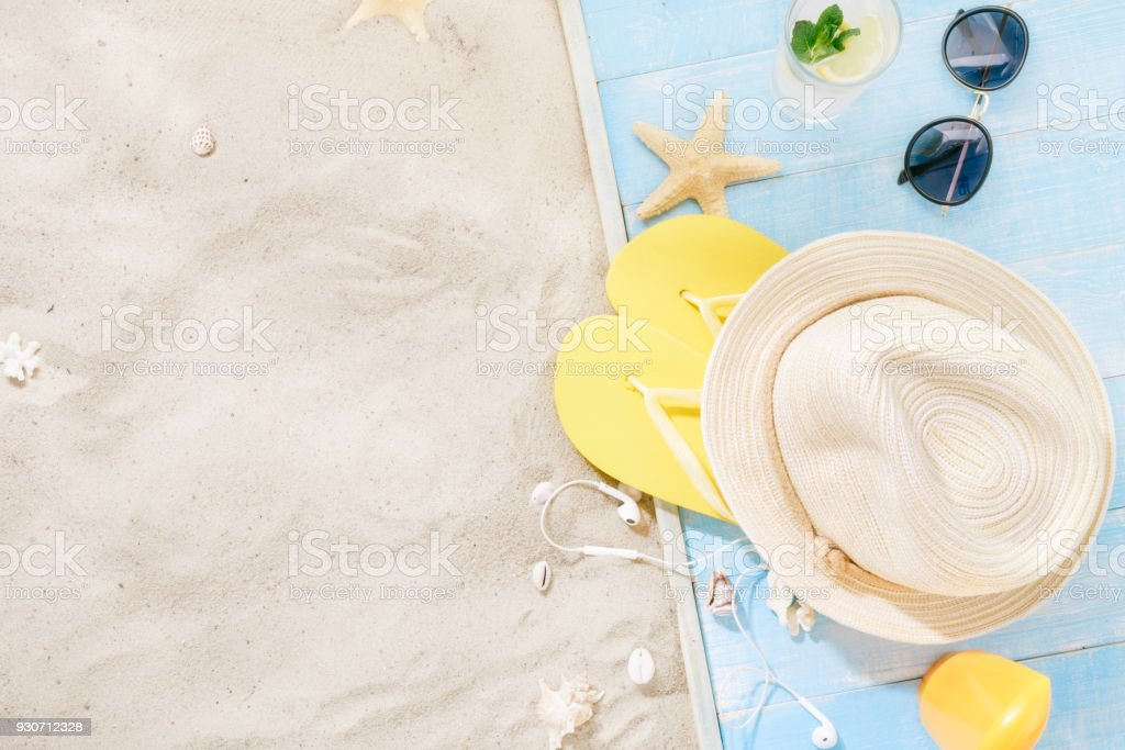 Travel vacation concept. Traveler accessories on sand. Straw hat, sunglasses, flip flops, cocktail, sunblock with copy space. Summer background stock photo