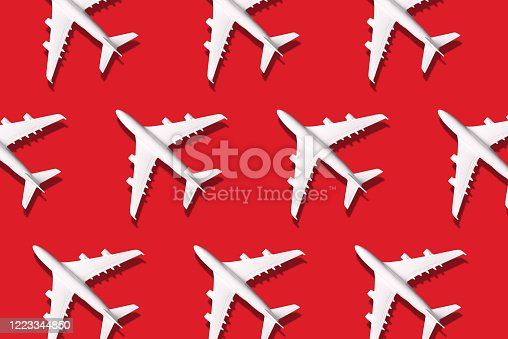 624266324 istock photo Travel, vacation concept. White model airplane on red color background with copy space. Top view. Flat lay. Minimal style design. 1223344850