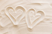 istock Travel, vacation, honey moon concept. Heart shapes on the sand. Love for two 1307229409