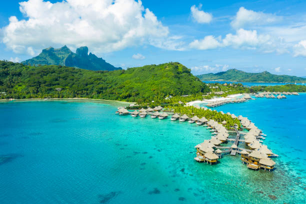 Travel vacation paradise aerial image with overwater bungalows in coral reef sea stock photo