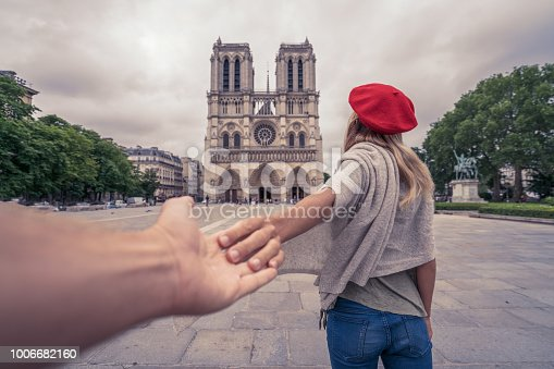 Follow me to concept- Young woman leading boyfriend to Paris at the Notre Dame cathedral.  People travel city concept, girl holding hand of partner inviting him to the city of lights. Love and romance.