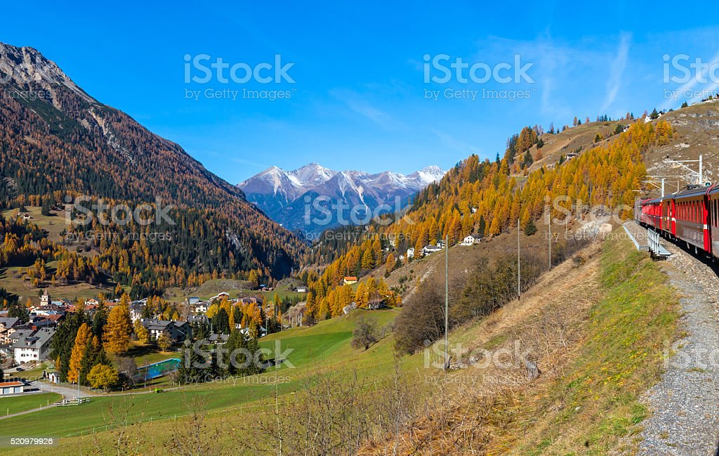 Travel with train in golden autumn Travel with train of Rhaetian Railway in golden autumn through the line of Glacier Express in Engadin, Canton of Grisons, Switzerland. Autumn Stock Photo