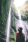 Travel woman Adventure and standing relaxation at Madakaripura waterfall East Java,IndonesiaIndonesia