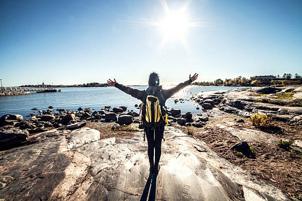 travel woman arms outstretched by the sea - finland stock pictures, royalty-free photos & images