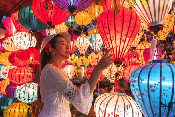 travel woman choosing lanterns in hoi an, vietnam - festival delle lanterne cinesi foto e immagini stock