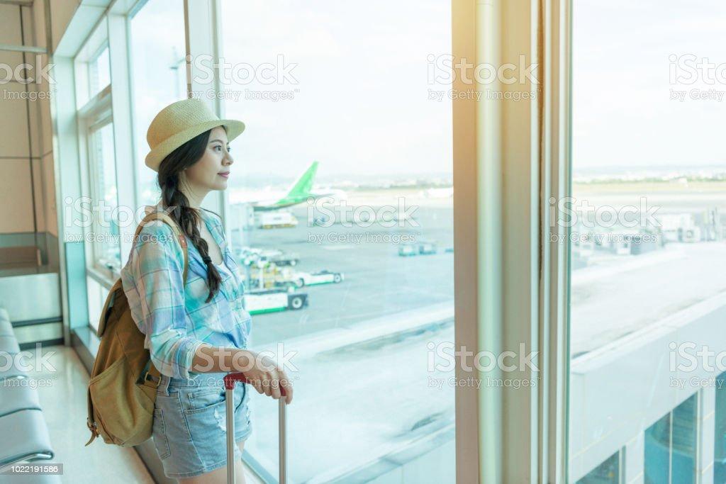 空港でウィンドウを見て女性を旅行します。 ストックフォト