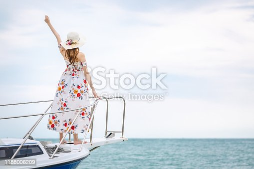 Summer vacation concept, Travel asian woman with dress and hat relax on sailboat in tropical sea at Pattaya, Thailand