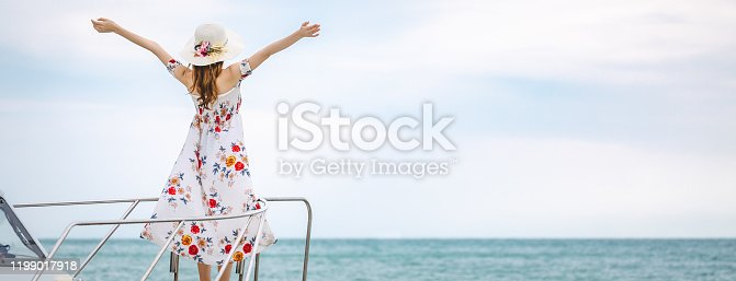 Travel summer vacation concept, Happy solo traveler asian woman with dress and hat relax on sailboat in tropical sea at Pattaya, Thailand