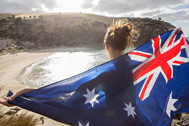 Travel woman stands on cliff above beach holding Australian's flag stock photo