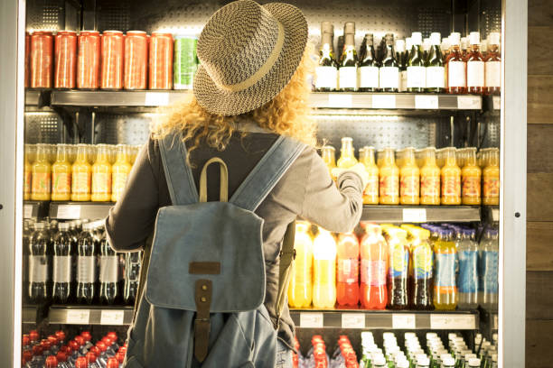 Travel woman viewed from back choosinf beverage in a fresh fridge - airport or station bar concept and traveler passenger choosing drinks - modern lifestyle backpack people buying drinks bottles stock photo