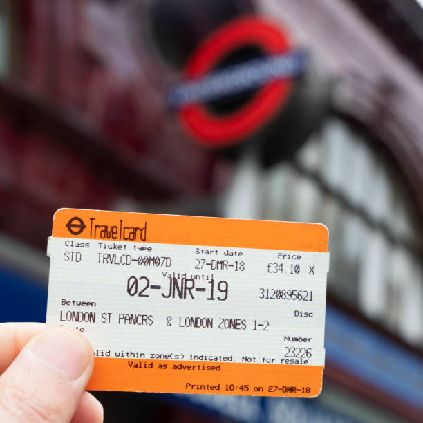 Travelcard ticket in London, UK London, UK - December 30, 2018: A man holds a Travelcard ticket in front of an underground station. This ticket allows to unlimited use of the different modes of transport in the Greater London area train ticket stock pictures, royalty-free photos & images