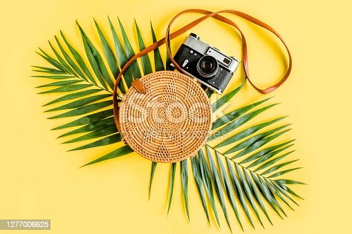 Traveler accessories concept on yellow background. Fashionable handmade natural round rattan bag, retro camera and tropical leaves. Stylish eco bamboo bag. Summer fashion concept.