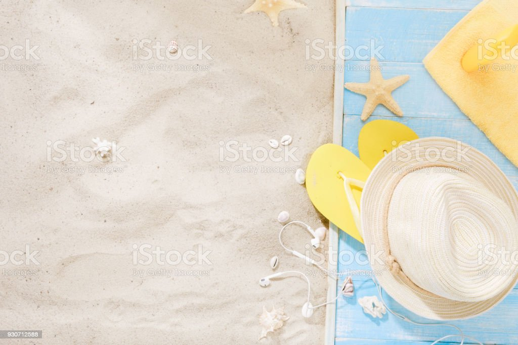 Traveler accessories on sand. Top view straw hat, flip flops, sunblock, towel, seashells with copy space. Travel vacation concept. Summer background stock photo