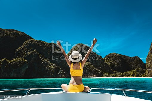 Travel summer vacation concept, Happy solo traveler asian woman with bikini and hat relax on boat in Maya Bay Phuket Thailand