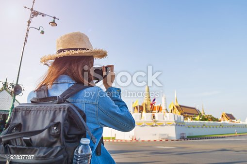 Back side traveler Asian woman in jeans jacket wearing a backpack take a picture by her camera to Wat Phra Kaew The Grand palace against the sky. one of favorite place in Bangkok Thailand.