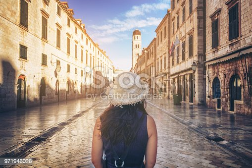 Traveler walks on the historic street of Stradun (Placa) in old town of Dubrovnik in Croatia - Prominent travel destination of Croatia. Dubrovnik old town was listed as UNESCO World Heritage in 1979.