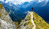 traveler at the edge of a cliff with amazing view behind him.Cascade Saddle, Mount Aspiring National Park, New Zealand