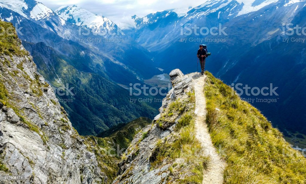 traveler at the edge of a cliff with amazing view behind him stock photo