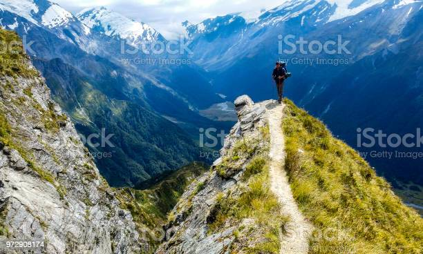 Photo of traveler at the edge of a cliff with amazing view behind him