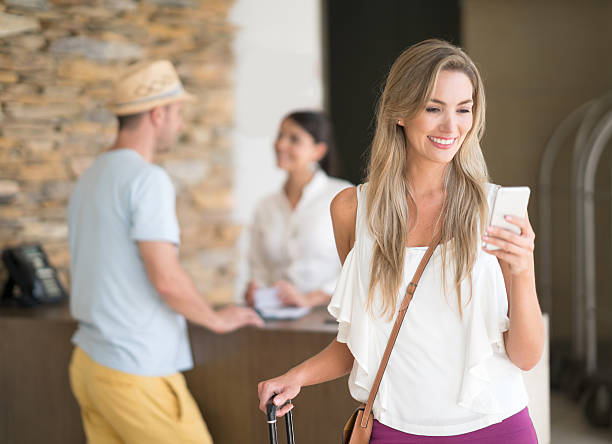 Traveler at the hotel using app on her cell phone stock photo