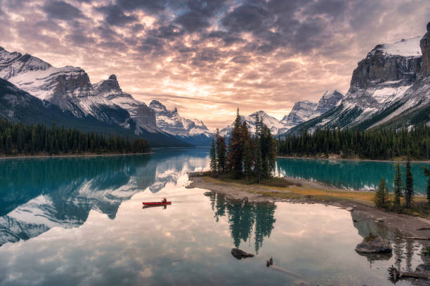 Traveler canoeing with rocky mountain reflection on Maligne lake at Spirit island in Jasper national park stock photo