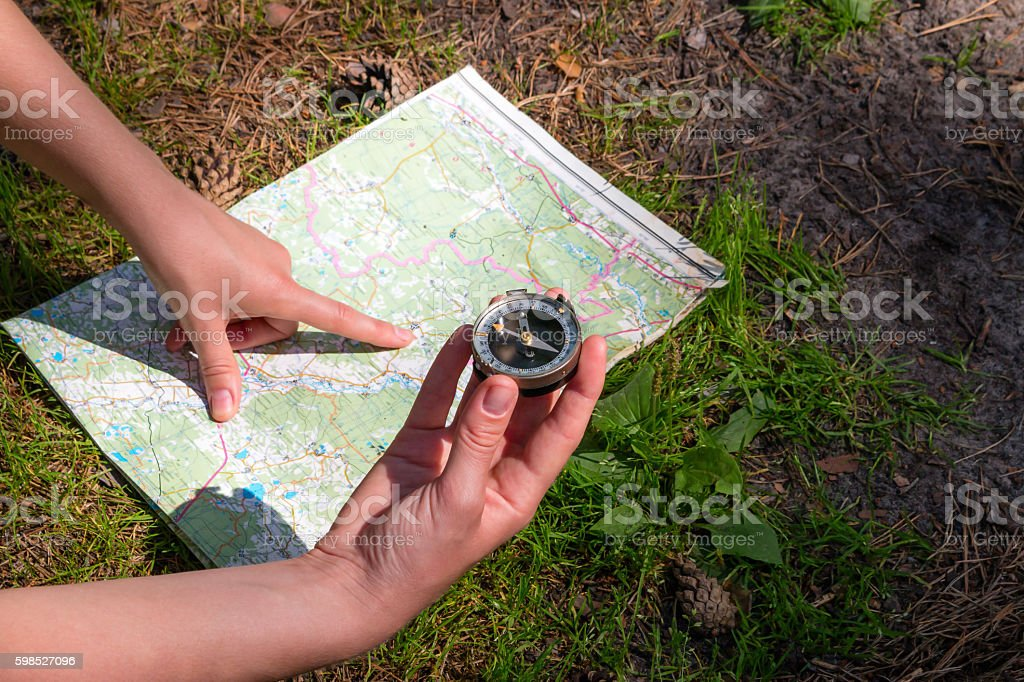 traveler checks with the route using a map and compass stock photo