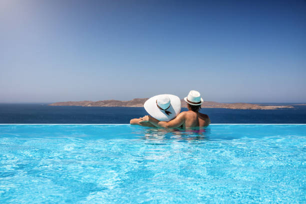 Traveler couple in a infinity pool enjoying the Mediterranean sea Traveler couple with sunhats hugging in a infinity pool and enjoy the view to the Mediterranean sea infinity pool stock pictures, royalty-free photos & images