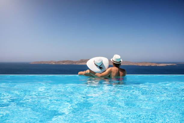 Reisendes Paar in einem Infinity-Pool genießen das Mittelmeer – Foto