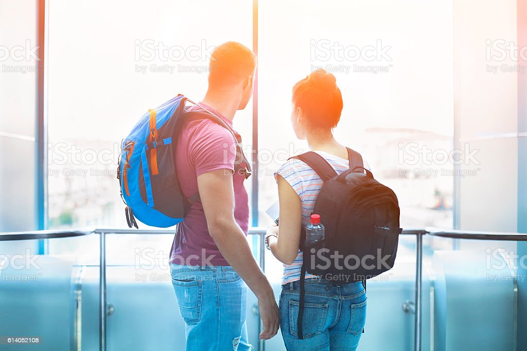 Traveler couple in love with backpacks indoors stock photo