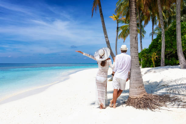 Traveler couple stands on a beautiful, tropical beach stock photo