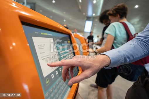 Traveler doing a self check-in at the airport using a machine and printing his boarding pass - travel concepts. **DESIGN ON SCREEN WAS MADE FROM SCRATCH BY US**