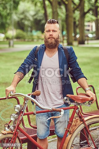 istock Traveler dressed in casual clothes with a backpack, relaxing in a city park after riding on a retro bicycle. 1026144772